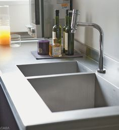 Acima, a cuba é de aço escovado com cantos retos (Mekal). A coifa (Tuboar) garante que o cheiro  dos alimentos não se espalhe pela casa. No recuo de gesso, lâmpadas amarelas T5 (Lumini). Projeto do arquiteto Diego Revollo.
