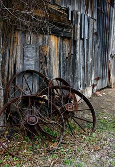 Old wagon wheels roll no more....they just rest beside old building!  Love this!!