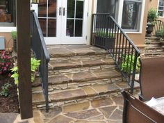 Flagstone steps and black iron rail leading down from screen porch in Charlotte, NC by Archadeck