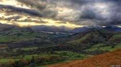 Landscape shot of the Lake District. The grey sky is thick with clouds.