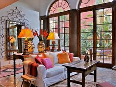 From the terra-cotta tile flooring to the tall arched French doors, this living room is a contemporary twist on traditional Spanish design. The warm accent colors look crisp against the white walls and sofa. The living room's color scheme is carried through to the adjacent traditional Spanish-style courtyard. Design by Carole Meyer