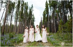 Bride and her bridesmaids who are wearing blush colored bridesmaid dresses walk down a path in the forest of Breckenridge with purple wildflowers growing all around them. - April O'Hare Photography http://www.apriloharephotography.com #Breckenridge #Colorado #ColoradoWedding #BreckenridgeWedding #BreckWedding #Blushbridesmaiddress