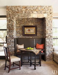 Stacked Napa stone lines the rustic sunroom's fireplace and walls, including this alcove's dining area | archdigest.com
