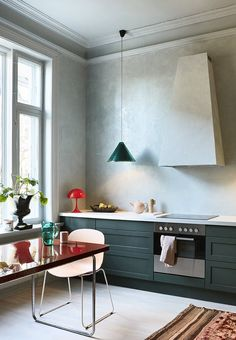Kitchen with the dominating colour being a deep, dark green that works well with the gray walls and red contrast elements.