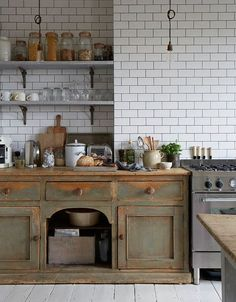A wooden cabinet provides a nice contrast to the sleek stainless steel shelves and cabinets in this kitchen, spotted on Houzz.