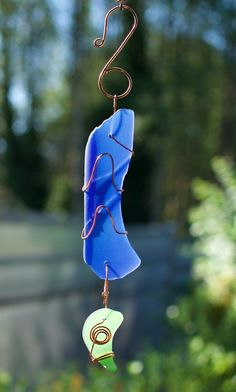 A beautiful glass and copper suncatcher- inspired by nature. The artist-made copper wrapped beach glass is smooth with a mat finish. This suncatcher measures 14 inches long from the top of the handcra