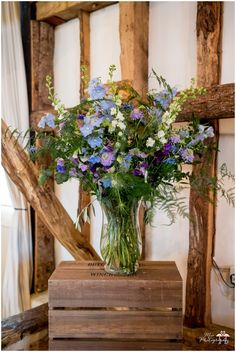 A large vase of Delphiniums, Scabious, Olive, Nigella, Asparagus Fern, Sweet Pea, Cornflower & Eucalyptus for the wedding ceremony at The Clock Barn. Flowers created by Eden Blooms Florist. Image by http://www.mia-photography.com/
