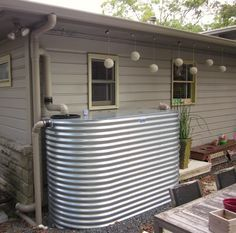 2,000 gallons of rainwater...love the corrugated tin look, it would blend in well with our outbuildings.