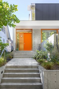 For a modern take on a traditional Seattle house (per the clients' request), Shed designed a concrete terraced front garden with a front door painted in Pure Orange. The exterior paneling is corrugated black metal and white, painted Hardie board. Orange Front Doors, Orange Door, Indoor Outdoor, Outdoor Living, Outdoor Decor, Urban Landscape, Landscape Design, Stem Challenge, Garage Door Design