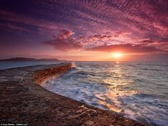 The Cobb sunrise, Lyme Regis, England: Clouds punctuate the sky above the choppy south coast of the UK in this energetic image. Waves lash the old stones of the Cobb, the town's harbour wall, as it extends into the distance, and the pale sun rises over Lyme Regis - 'The Pearl of Dorset'