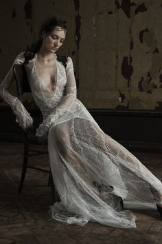 Light ivory deep V-neck long sleeve Chantilly lace soft mermaid gown with plunging back and hand applique silk flower accents on the cuff and train. Styled with black passementiere bolero and Chantilly lace panty.
