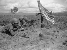 . GI\'s guarding an artillery outpost on Korea\'s west-central front on June 9, 1951 make sure the Chinese  will know they are facing U.S. soldiers . Standing guard under stars and stripes waving from a carbine are, left to right: Pvt. William Jones, Havre De Grace, Md.; Pfc. Roderick Fernandez, Laurelton, New York City; and Pfc. James Garrick, Dickinson, Ala. (AP Photo/Robert Schutz )