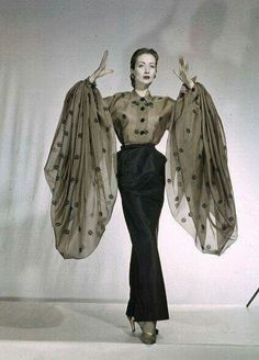 Della Oake is wearing organdy blouse with voluminous sleeves and long slim satin skirt by Schiaparelli, 1951.
