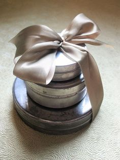 tins tied with a big satin bow...quick & easy idea for gift-wrapping... glue magnets to tins to keep together