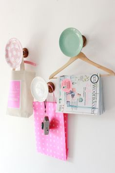 Pastel pastry plates mounted on wooden pedestals—Teresa of Vintage Rose Brocante used pieces of a coat rack—make a cheery kitchen hook display. Tote bag straps won't slip off, while the addition of wooden hangers transforms them into racks for magazines or coats.