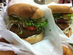 Vegan seitan burger with avocado, tomato, sprouts, red onion and herb veganaise on an organic whole wheat roll.