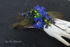 Prom Flowers - Wrist corsage of blue Delphinium florets and green Hypericum berries accented with Peacock feathers.