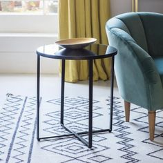 Toledo Side Table  Make a statement with this trendy side table featuring a contemporary smoked grey glass top set in a matt black metal frame with stylish cross frame detailing for strength and stability.