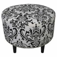 """Upholstered ottoman with a damask motif and foam padding. Made in the USA.  Product: OttomanConstruction Material: Wood, fabric and foamColor: Black and whiteFeatures: Made in the USADimensions: 19"""" H x 23"""" Diameter"""