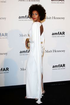 At Milan Fashion Week in September, Solange makes a simple white dress pop with red lipstick and metallic accessories.