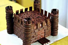 Its a chocolate castle. 2 square cakes on top of one another with icing, . cookies for the towers,( a wee bit of icing in between cookies for gluing them together ) chocolate bar pieces for brick . kit kat chocolate slab for Drawbridge. Chocolate Frosting, Chocolate Cookies, Vanilla Cookies, Torta Chocolate, Butterscotch Cookies, Twix Cookies, Chocolate Biscuits, Shortbread Cookies, Cake Cookies