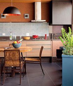 A churrasqueira, já existente no imóvel, ganhou a companhia de cozinha gourmet, no projeto do escritório de arquitetura Contrera e Biarari. O porcelanato escuro no chão disfarça a sujeira