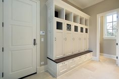 White storage lockers and drawers with a ledge to sit to put on shoes. Doorway leads into a hallway.