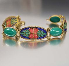 Gorgeous and very rare plique-a-jour enamel sterling silver bracelet from the Art Nouveau era. Gold over sterling ornate curved links have colorful plique a jour enamel geometric floral style shapes a