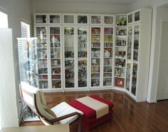 Billy bookcases from IKEA, with height extensions and glass doors.  We used solid shelves for our manga collection and glass shelves + lights for our Transformers collection.  There is also a glass display case from IKEA on the left, but it didn't come out well in the photo.  The chair is also from IKEA (we've had the chair for years!).