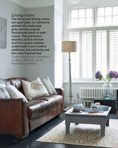 Stark white walls, white shutters, tan distressed sofa. A heavenly mix!!! LOVE.