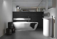 Moderne badkamer met losstaand bad. De lijnen van deze badkamer zijn op zijn minst strak te noemen. Het minimalistische ontwerp komt goed tot zijn recht door de gietvloer en het lijnenspel van de muurtegels achter het bad. Deze worden nog eens versterkt door de badkraan en het planchet boven de wastafel. De wastafelkraan staat helemaal los van de wastafel en trekt daardoor direct de aandacht.