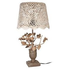 """Add artful appeal to your home library or living room with this eye-catching table lamp, showcasing a lace-inspired shade and floral base.  Product: Table lampConstruction Material: Glass, resin, wood and fabricColor: TanAccommodates: (1) 75 Watt bulb - not includedDimensions: 20"""" H x 10.3"""" Diameter"""