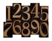 ten arabic numerals 0-9 in vintage wood letterpress blocks stained by black ink, flipped horizontally, isolated on white  stock photography
