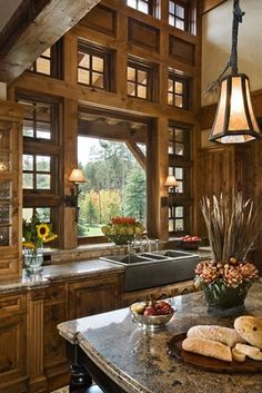 A rustic kitchen is filled with light from high transom windows.