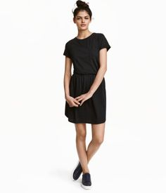 Black. Short dress in soft jersey. Chest pocket, short sleeves with sewn cuffs, side pockets, elasticized seam at waist, and gently rounded hem.