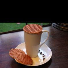 """The Stroopwafel – or """"syrup waffle"""" – is a traditional Dutch cookie originating from Gouda in the Netherlands. No one is certain when people began baking them; one story dates the first stroopwafel in 1784. A baker made cookies out of crumbs from his left over baked goods and put the warm syrup between the cookies. The first known recipe for Stroopwafels dates back to 1840.  Traditionally, Stroopwafels are placed on your coffee cup to heat them through. The steam from the coffee heats and war..."""
