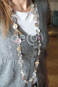 Collana lunga con bottoni in madreperla bianchi e lilla, alternati da cristalli grandi e cristalli piccoli inseriti sopra ogni bottone. Possibilità di fare due giri. Chiusura a calamita