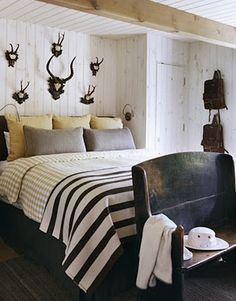White walls means you can do much. Notice graphic elements above headboard and on striped blanked at foot of bed.Rustic graphic bedroom.