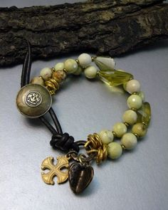 This piece is made with rich, yellow citirne nuggets that range in size from 14-16mm and lovely 10mm lemon chrysoprase gemstone beads. The lemon chrysoprase beads are faceted and contain hues of brown, white, and lime green. Soft brown leather slips easily around the eclectic button. The knot in the leather can be adjusted fitting a larger wrist size. A brushed Byzntine cross and hammered heart add charm to this bright, original piece. Ooak