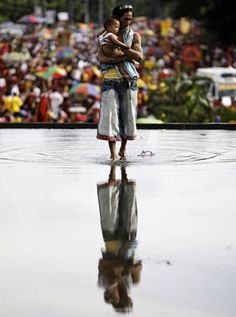 January 9, 2012 A Filipino devotee carries a child across a pond of water as they wait for the wooden image of Jesus Christ known as the Black Nazarene to pass by during it's feast day in Manila, Philippines. Millions of Roman Catholic devotees paraded under a massive police cordon after Philippine President Benigno Aquino III warned that terrorists might target the annual procession. Aaron Favila/AP//the day I moved to Manila
