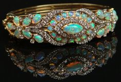 Very Fine Quality Important Mid Century Modern Hand Made Opal, 3.5 to 4.0 Carats Diamond, 14 Karat Yellow Gold and Platinum Bangle Bracelet Set with 30 White Opals and Accented Throughout with Approximately Round Brilliant Cut Diamonds. Opals with Red Green and Blue Play of Color. Diamonds F-G Color, VS1-VS2 Clarity. Artist Signed Casbah.