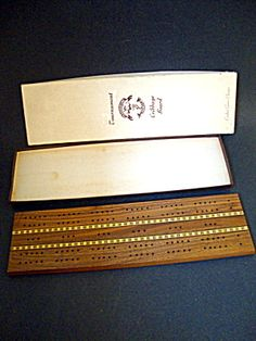 A vintage cribbage board in the original box. Measures 15.75 in. x 4.25 in. Marked Pleasantime Games. 1950's era. Tournament Crafted Game Classics. Very good condition.