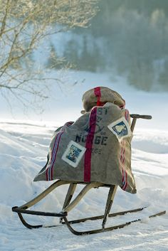 mail bag on old sleigh - I love the idea of putting packages for different families you visit in one big burlap sack (decorated with tags & a message) and using it year after year