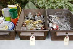 """5. Avoid pricing every little thing. Sort goods in bins, like these metal breadboxes (pictured above), and stick a single """"for each"""" tag on the lot. If you must mark all your gear, opt for color-coding with labels, and then tack up a prominent key that notes each hue's corresponding cost. 6. Teach old items new tricks. Instead of stacking clipboards atop a table, Lane hangs them on a wall as impromptu frames. Her cake stands serve as pedestals for pillar candles. A dish drainer might…"""