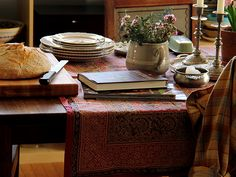 So cozy, a table set with candles, fresh flowers, warm bread and books!