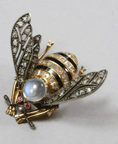 Victorian bee brooch is rendered in 18k gold, enamel, moonstone and rose diamonds. The head is set with a gem quality cabachon moonstone that is clear and blue, exhibiting that beautiful sheen known as adularescence. The details are fine, right down to the antennae which are set with tiny diamonds on their tips. The eyes are faceted rubies