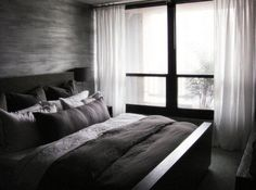 Minimalist bedroom in dark colors and contrasting white drapes by TROST