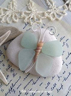 What a sweet butterfly paperweight or little piece of nautical decor made from sea glass, a weathered beach stone, and a shell.