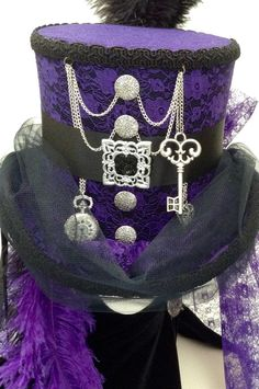 Purple lace Steampunk top hat, features include silver chains, buttons, pocket watch heart charm and key.  Face veil in black, ostrich feathers crown and dropped side and rear purple back veil at waist length, black satin ribbons side and rear. Made in my own workshop in Scotland  https://www.etsy.com/uk/shop/Blackpin?ref=hdr_shop_menu