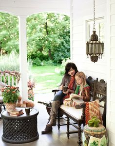 Victorian-style furniture and floral accents gives this porch an indoor comfort feel.